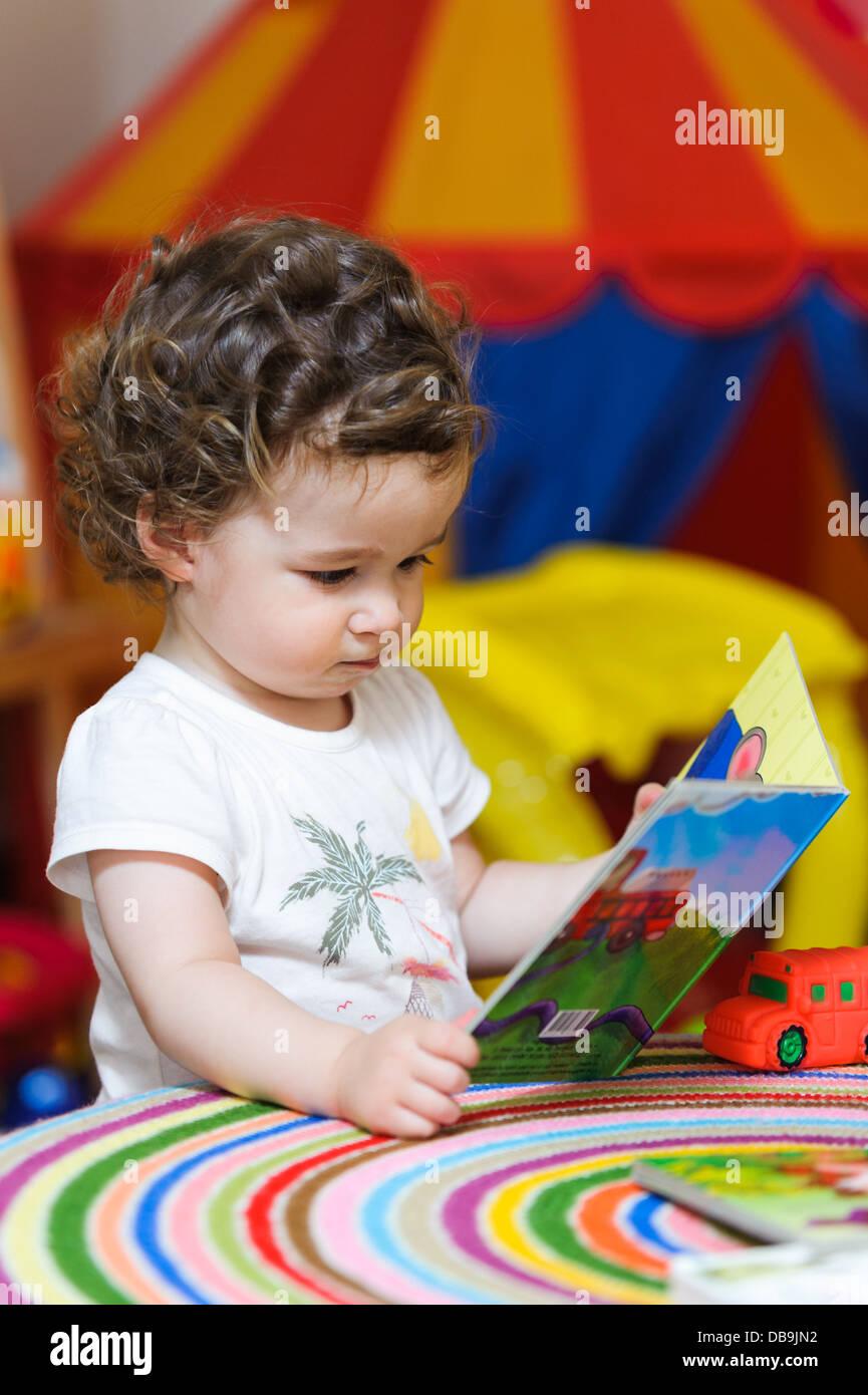 Il bambino in età prescolare ragazza alla ricerca di un libro di fotografia Immagini Stock