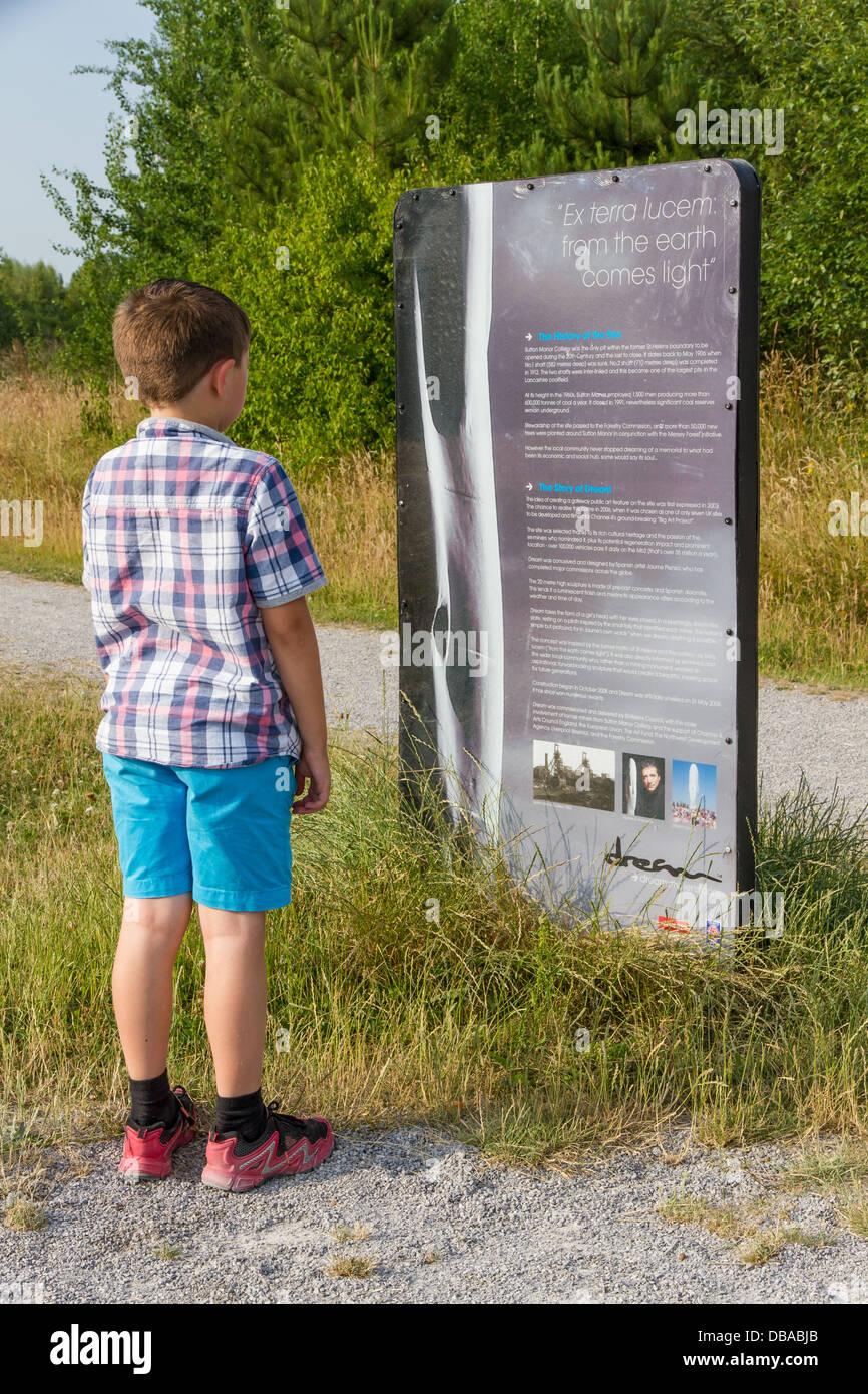 Ragazzo giovane durante la lettura di una scheda di informazioni circa il sogno di una scultura in grassetto Forest Immagini Stock