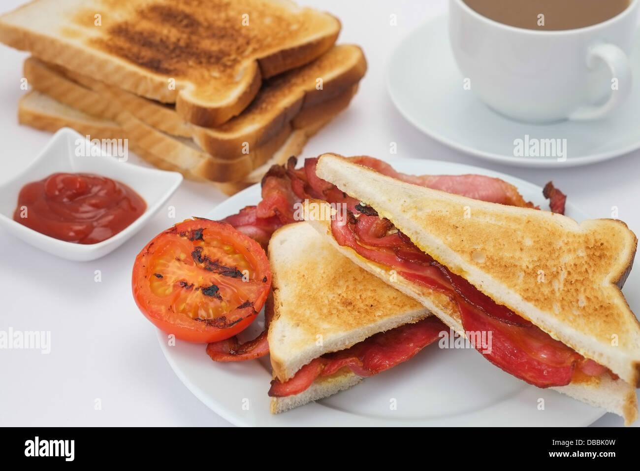 La prima colazione di bacon sandwich con pane tostato e una tazza di caffè Immagini Stock