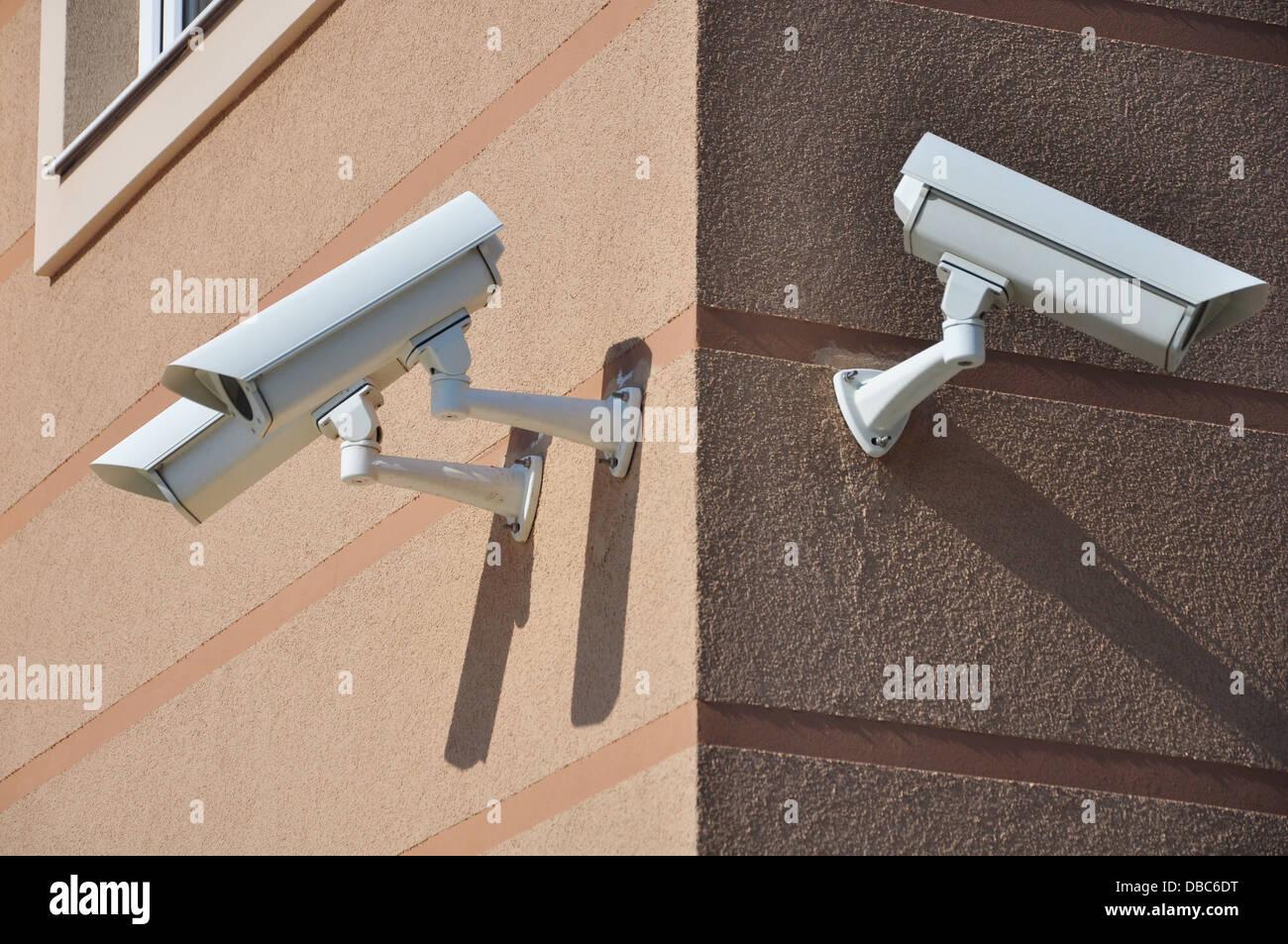 Edificio con le telecamere di sicurezza guardando intorno Immagini Stock