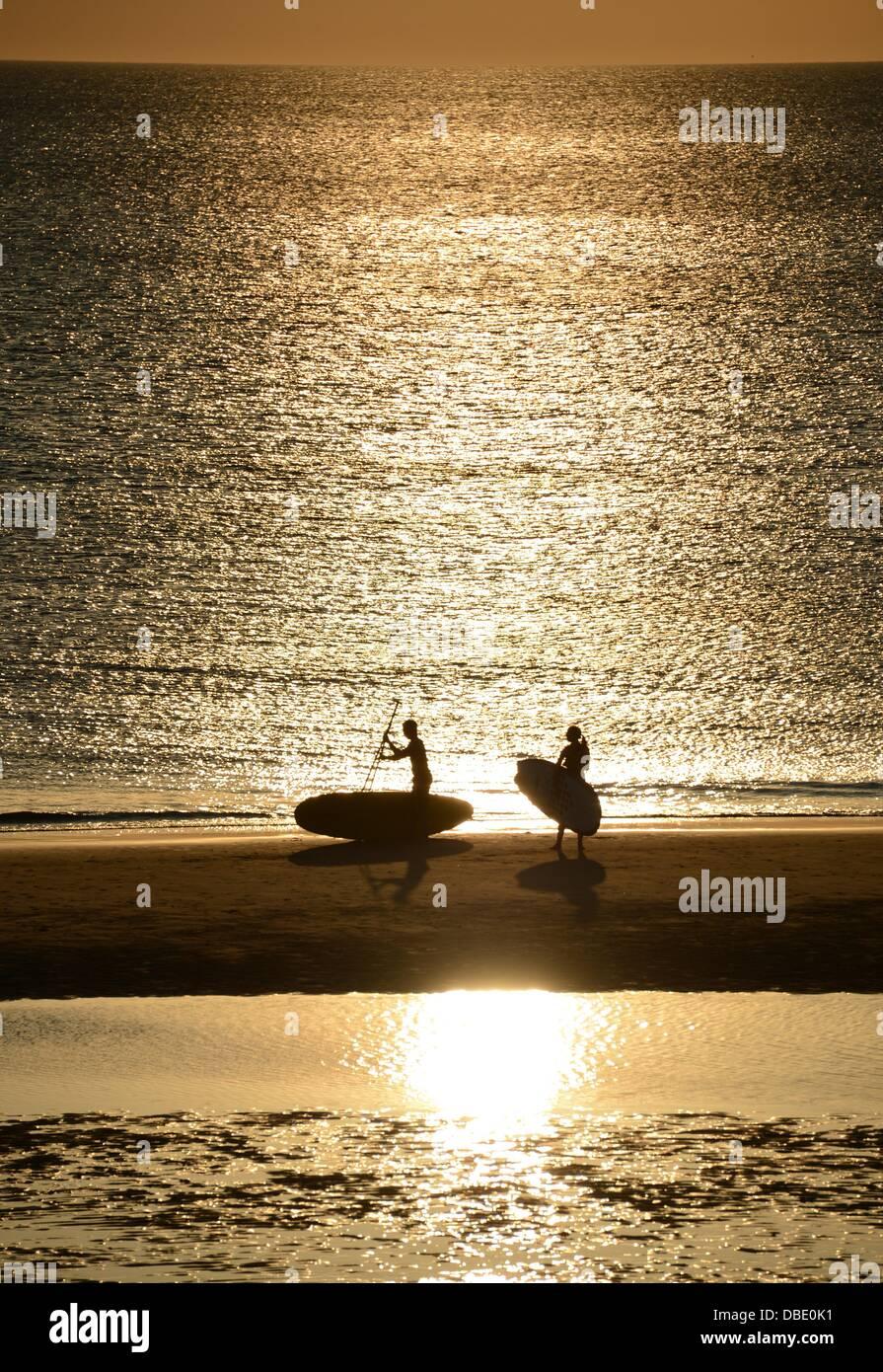 Surfers uscire dall'acqua e proseguire a piedi lungo la spiaggia nella luce del sole al tramonto sulla spiaggia Immagini Stock