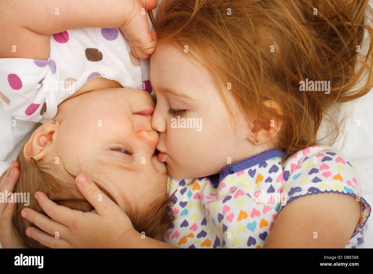 Vecchia sorella kissing baby a letto Immagini Stock