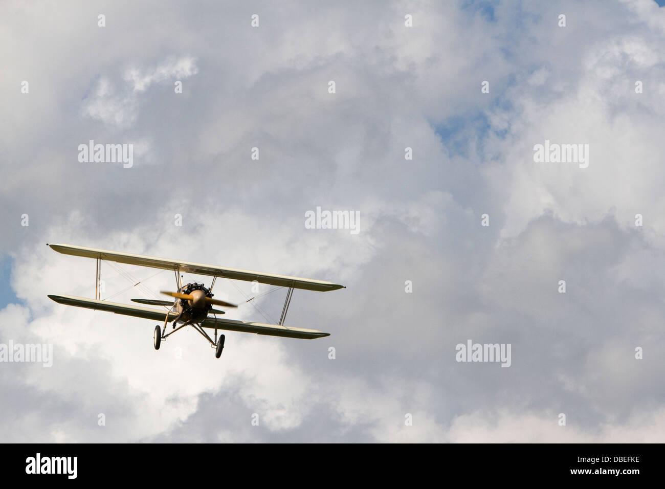 Un biplano in volo contro un cielo blu con nuvole cumulus. Immagini Stock