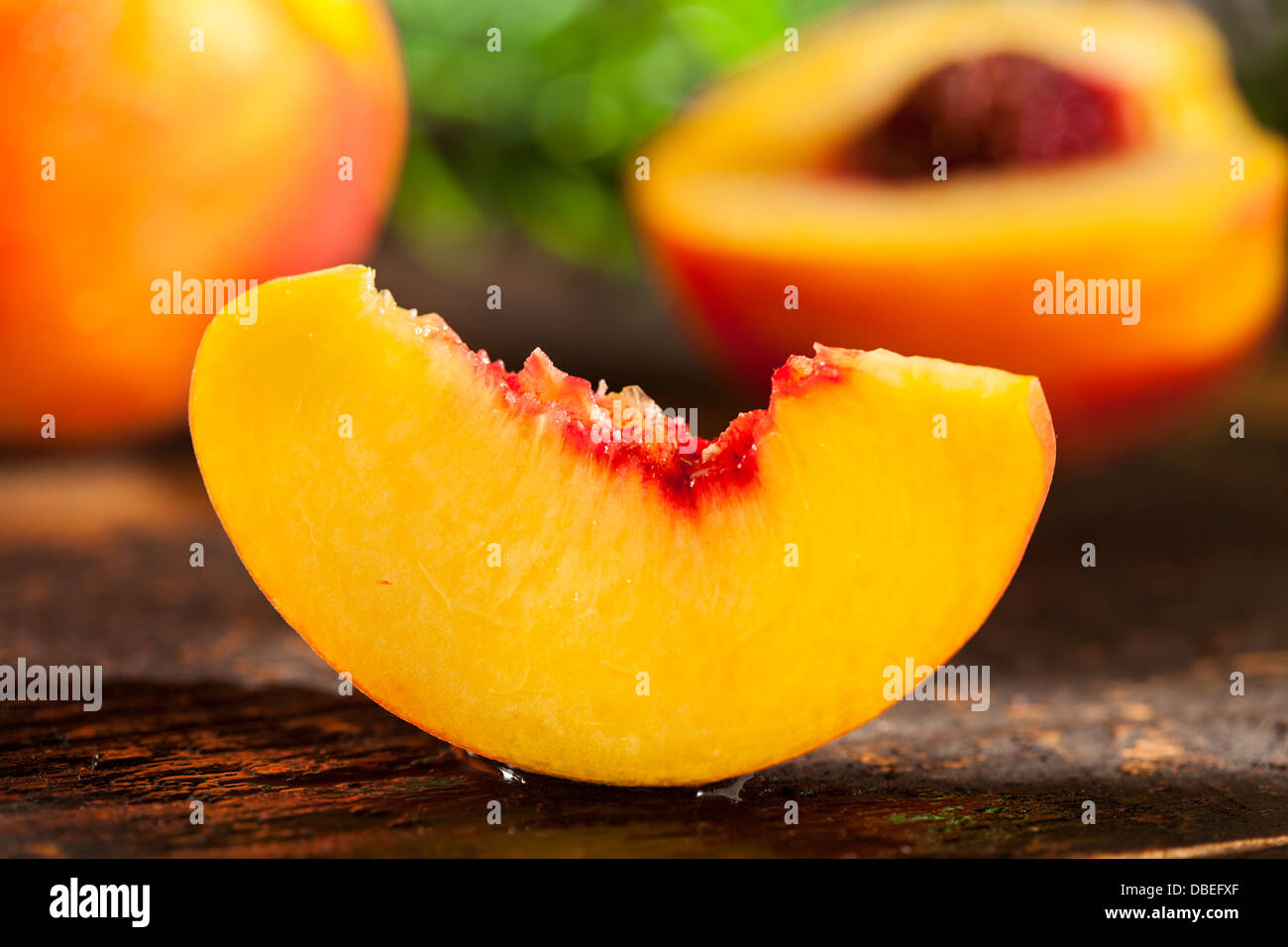 Organici di arance mature le pesche su uno sfondo Immagini Stock