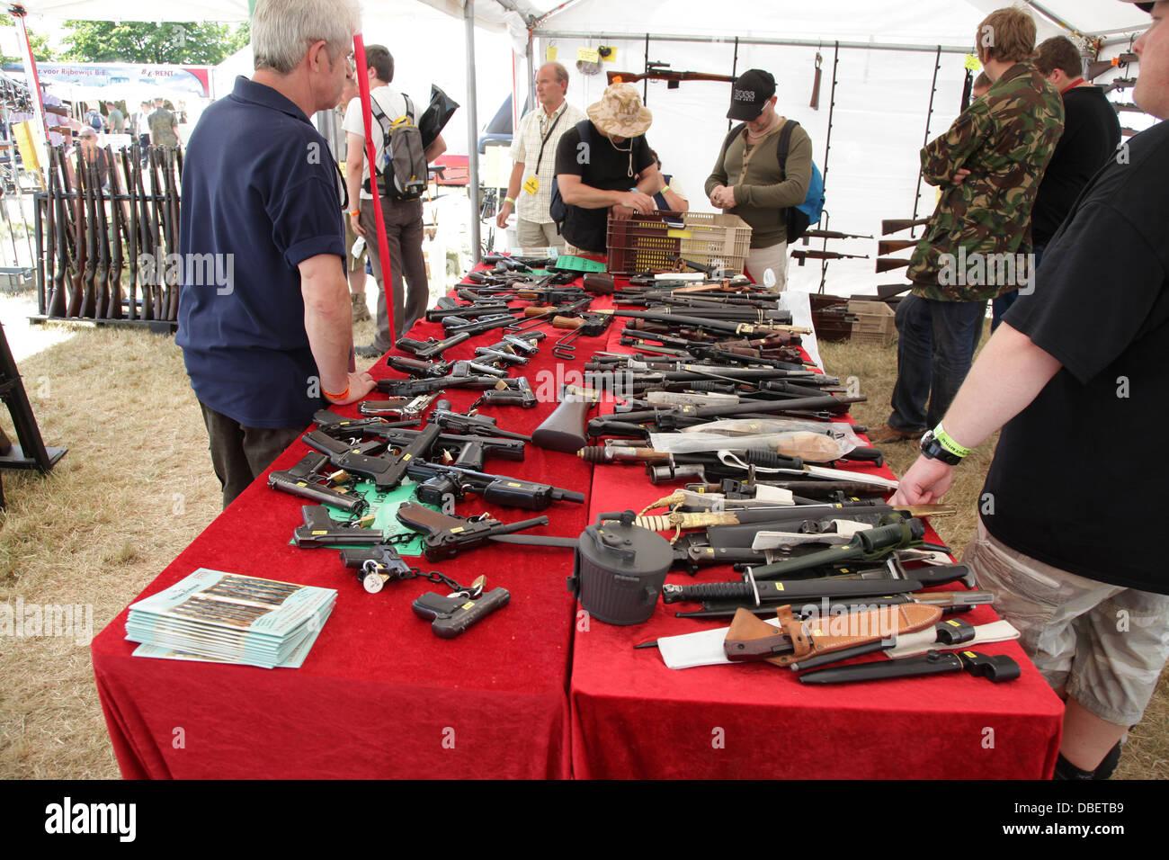 Le persone che ricercano pistole a un militare e Fiera di armi Immagini Stock