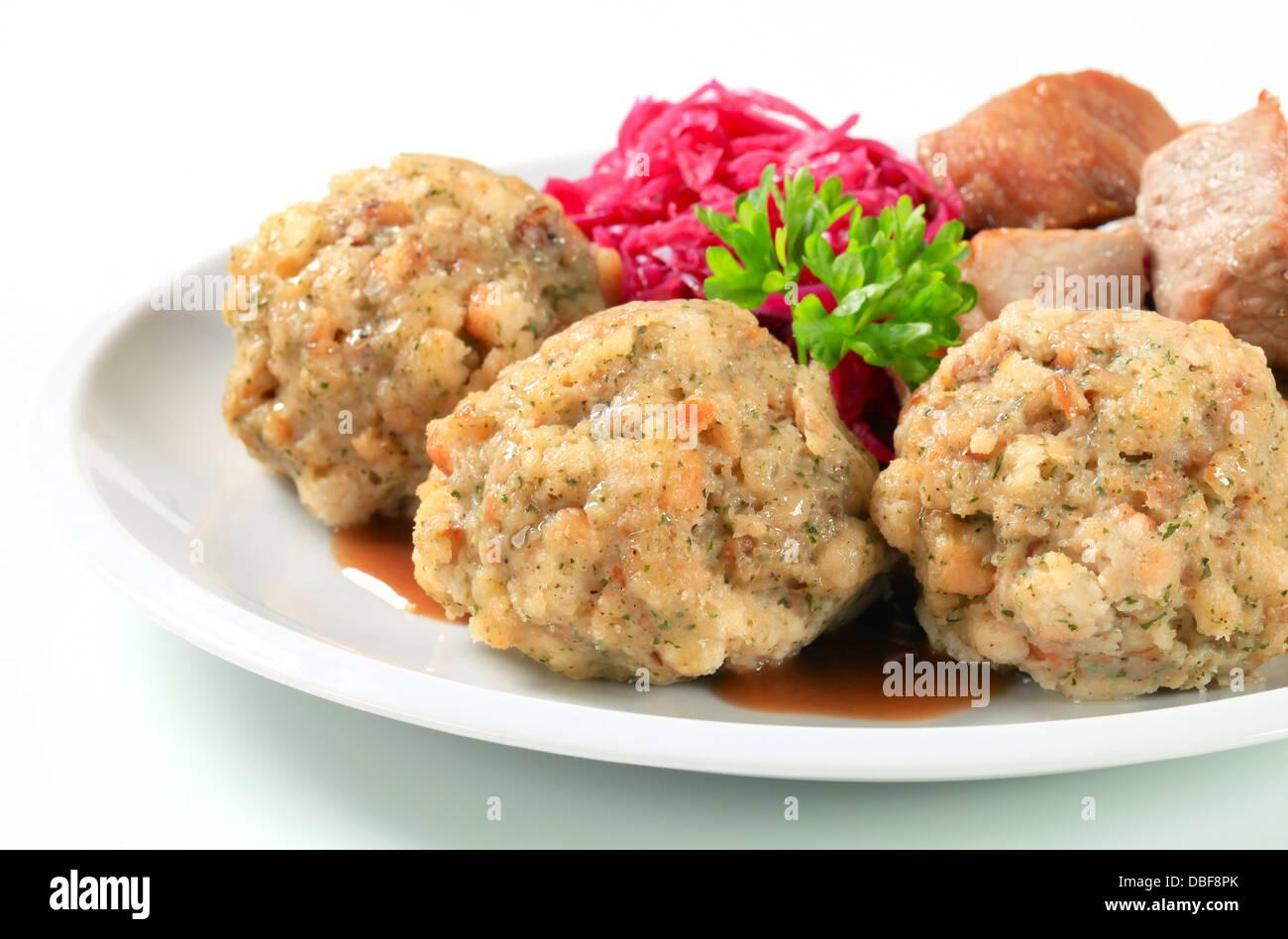 Piatto di arrosto di maiale con canederli tirolesi e rosso kraut Immagini Stock