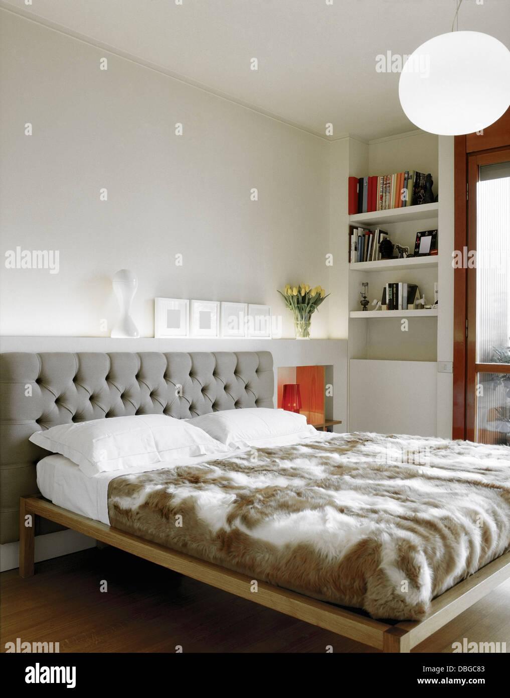 Letto moderno per una camera da letto con libreria e pavimento in ...