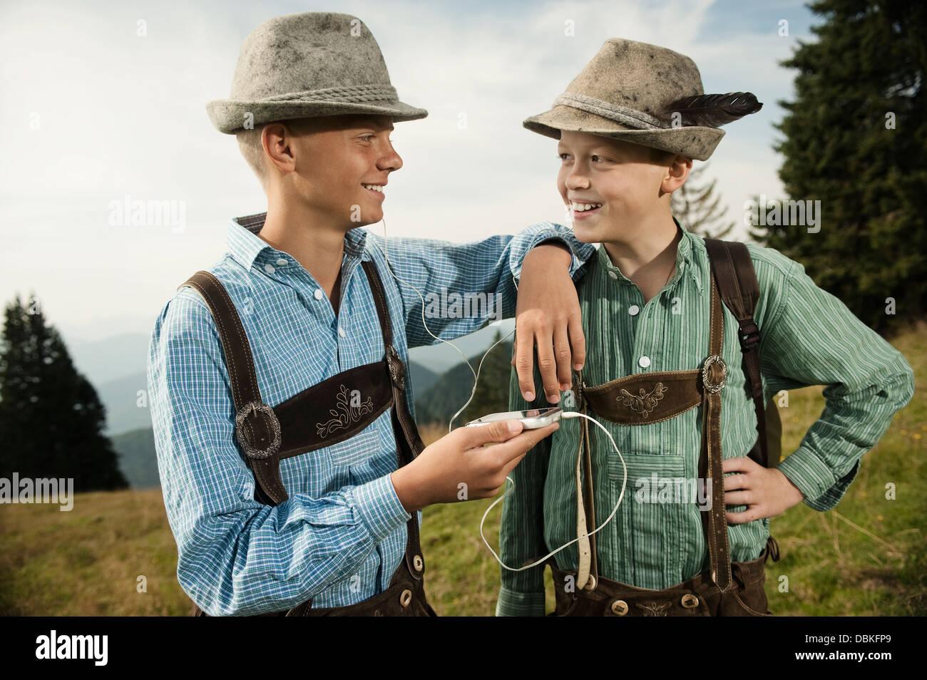 In Germania, in Baviera, due ragazzi in abbigliamento tradizionale utilizzando smart phone Immagini Stock