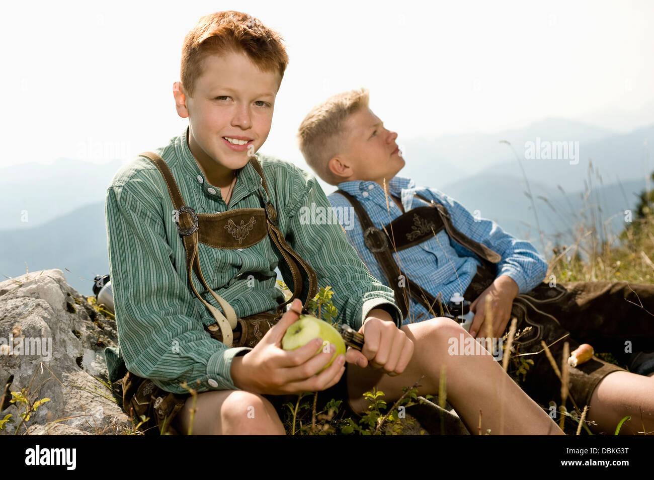 In Germania, in Baviera, due ragazzi in abbigliamento tradizionale di prendere un periodo di riposo in montagna Immagini Stock