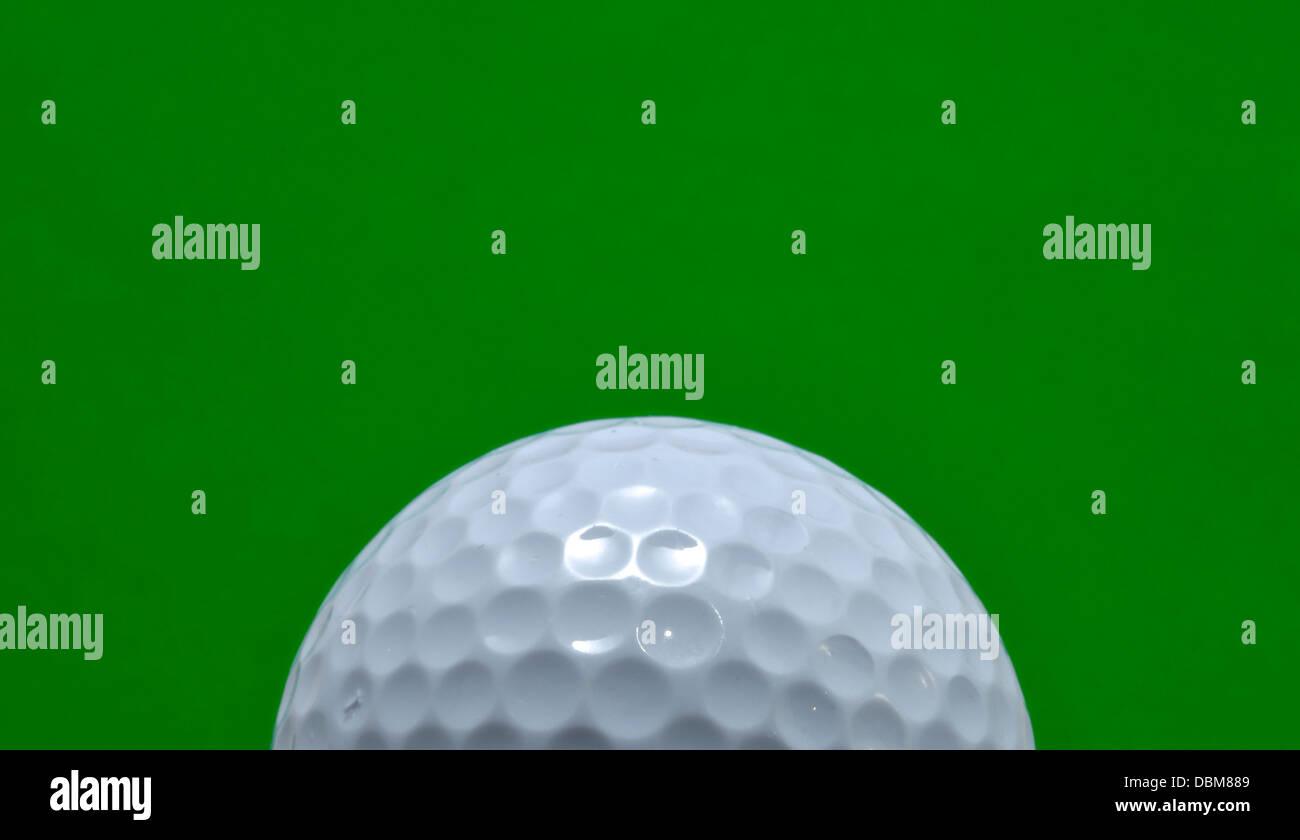 Palla da golf isolata su uno sfondo verde, spazio di copia Immagini Stock