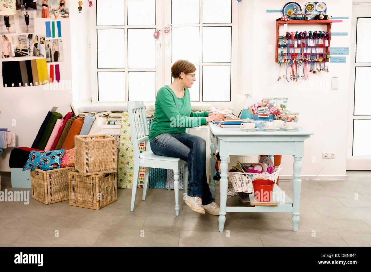 Donna che utilizza computer portatile in negozio, Monaco di Baviera, Germania, Europa Immagini Stock