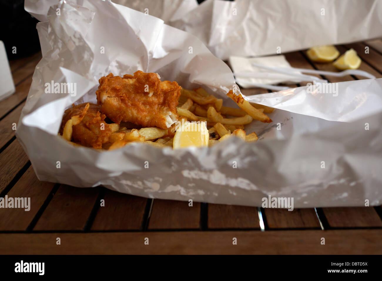 Pesce, patatine in involucro di carta dal ristorante a harbor Kalk Bay nei pressi di Città del Capo Immagini Stock
