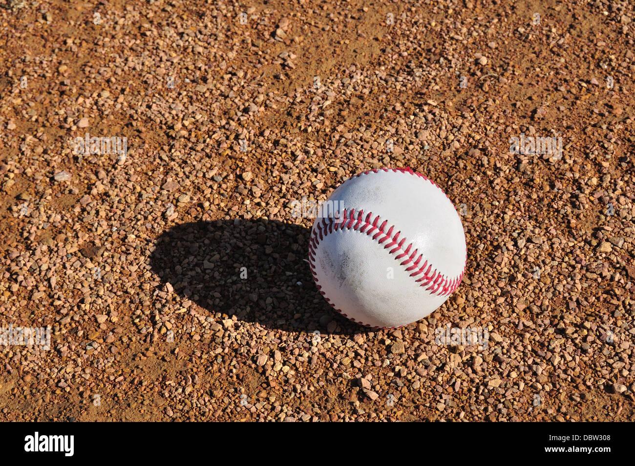 Il baseball a terra su un diamante di baseball Immagini Stock