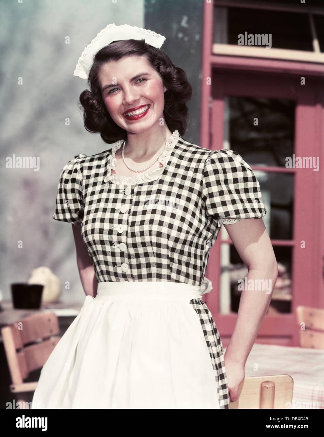 72cffa53d2e7 Negli anni quaranta anni cinquanta sorridente donna vestita di nero e bianco  a scacchi cameriera vestito Abito in pizzo CATENARIA CAP guardando la ...