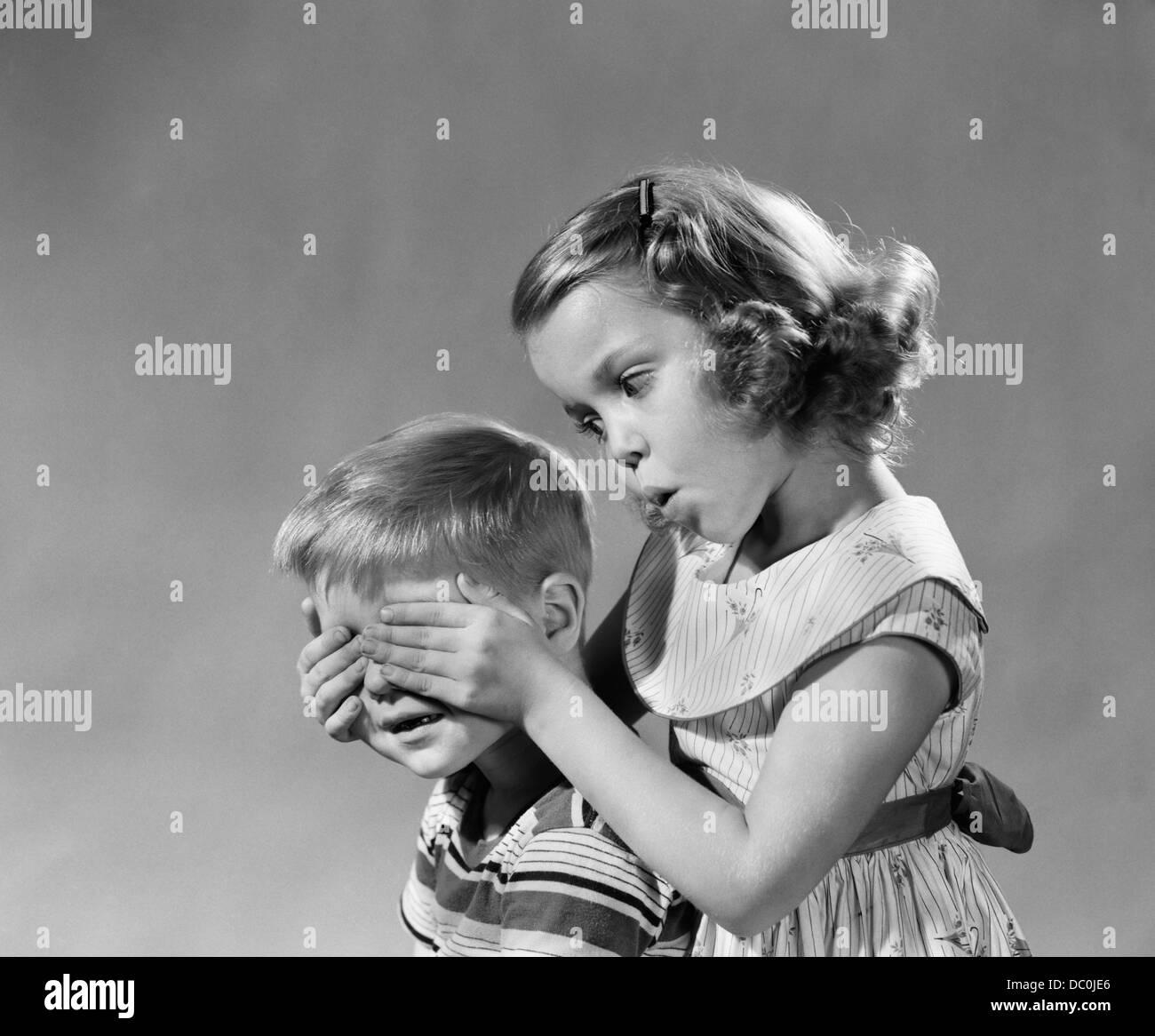 Anni Cinquanta anni sessanta indovinare chi ragazza trattiene la sua mano sopra gli occhi dei ragazzi ciechi eccitante Immagini Stock