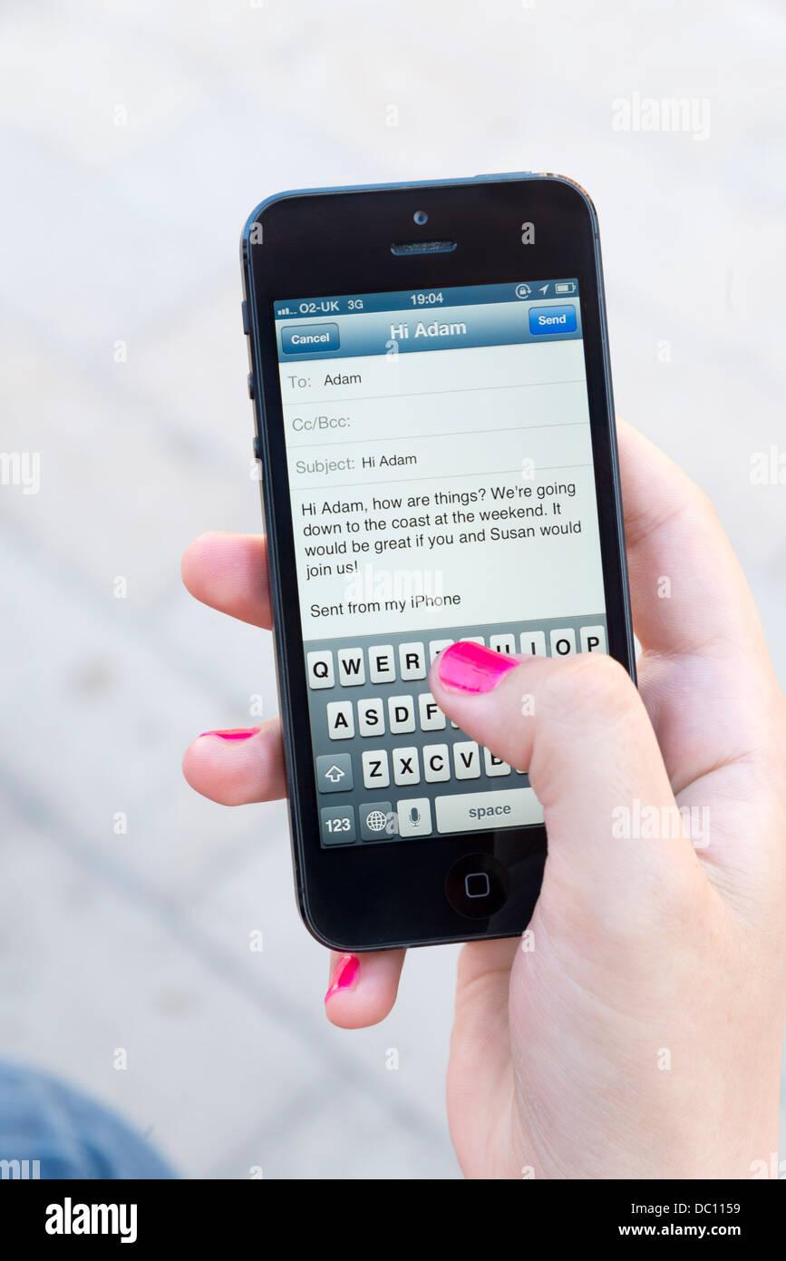 Donna inviando un messaggio di posta elettronica su Apple iPhone 5 Immagini Stock