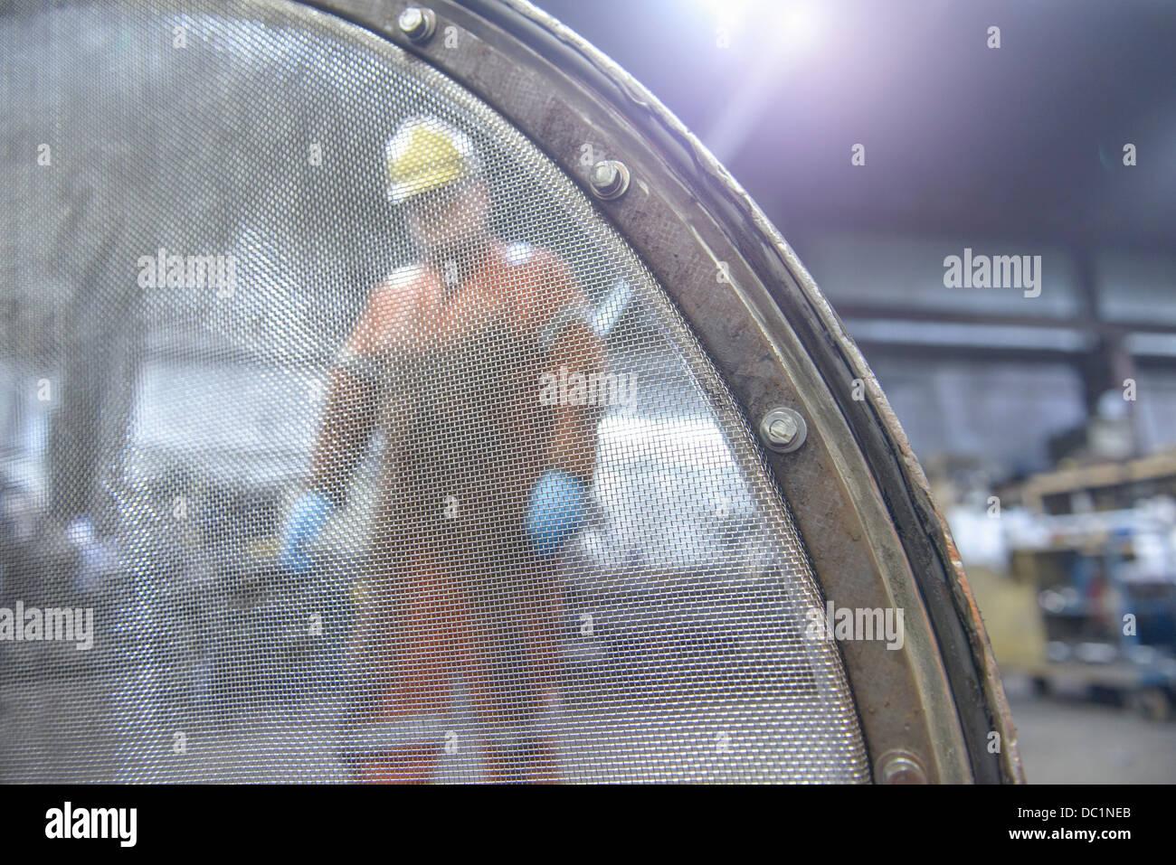Ritratto di lavoratore dietro il crivello industriale nella fonderia di acciaio Immagini Stock