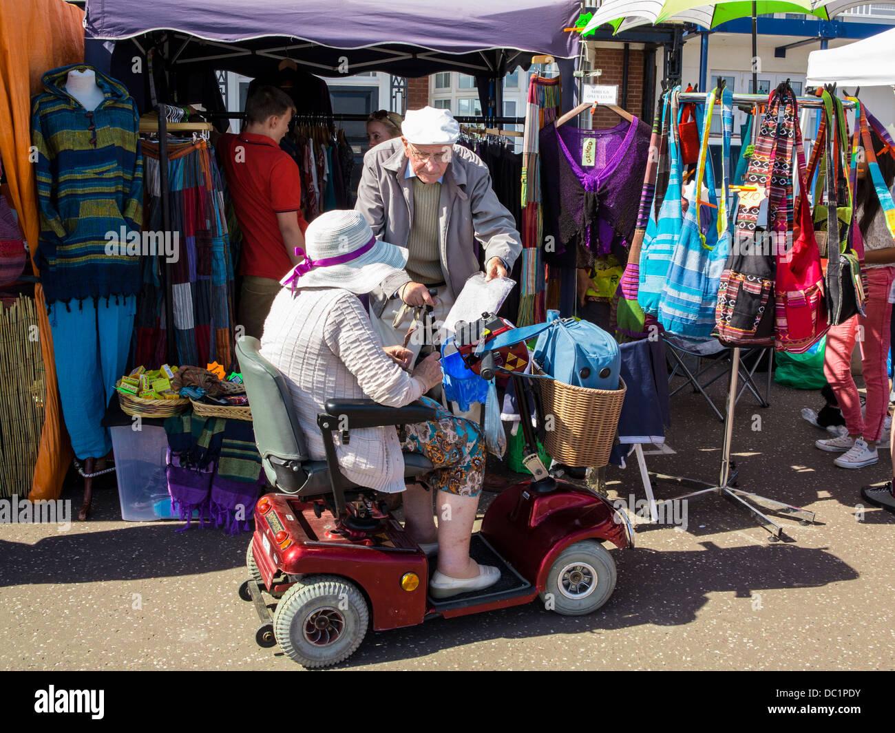 Coppia di anziani a fare shopping con la mobilità scooter a Sidmouth, nel Devon, Inghilterra Immagini Stock