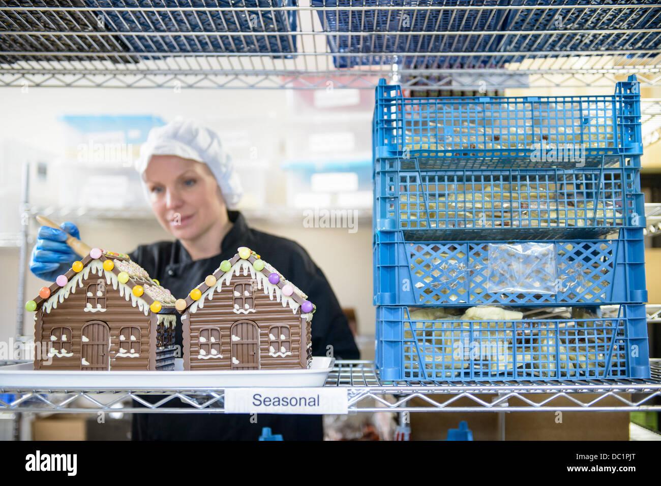 Chocolatier applicare decorazione di case di cioccolato Immagini Stock