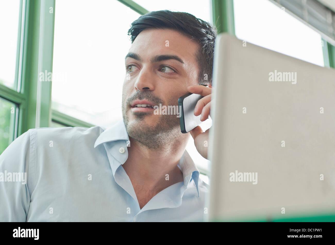 Chiusura del giovane maschio lavoratore di ufficio parlando al telefono cellulare Foto Stock