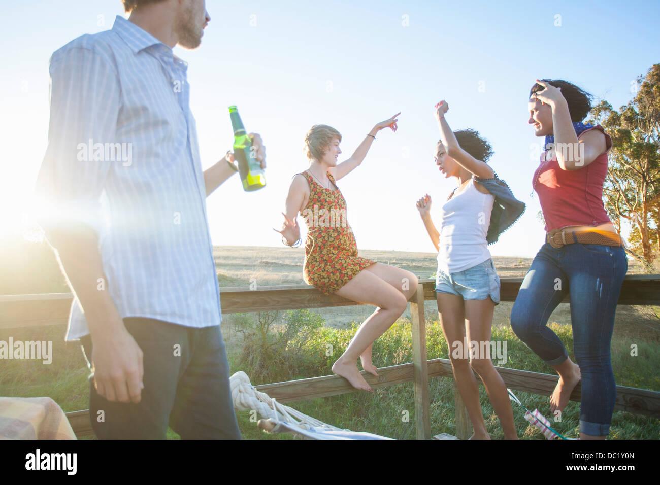 Giovane uomo guarda amici danza sul balcone Immagini Stock