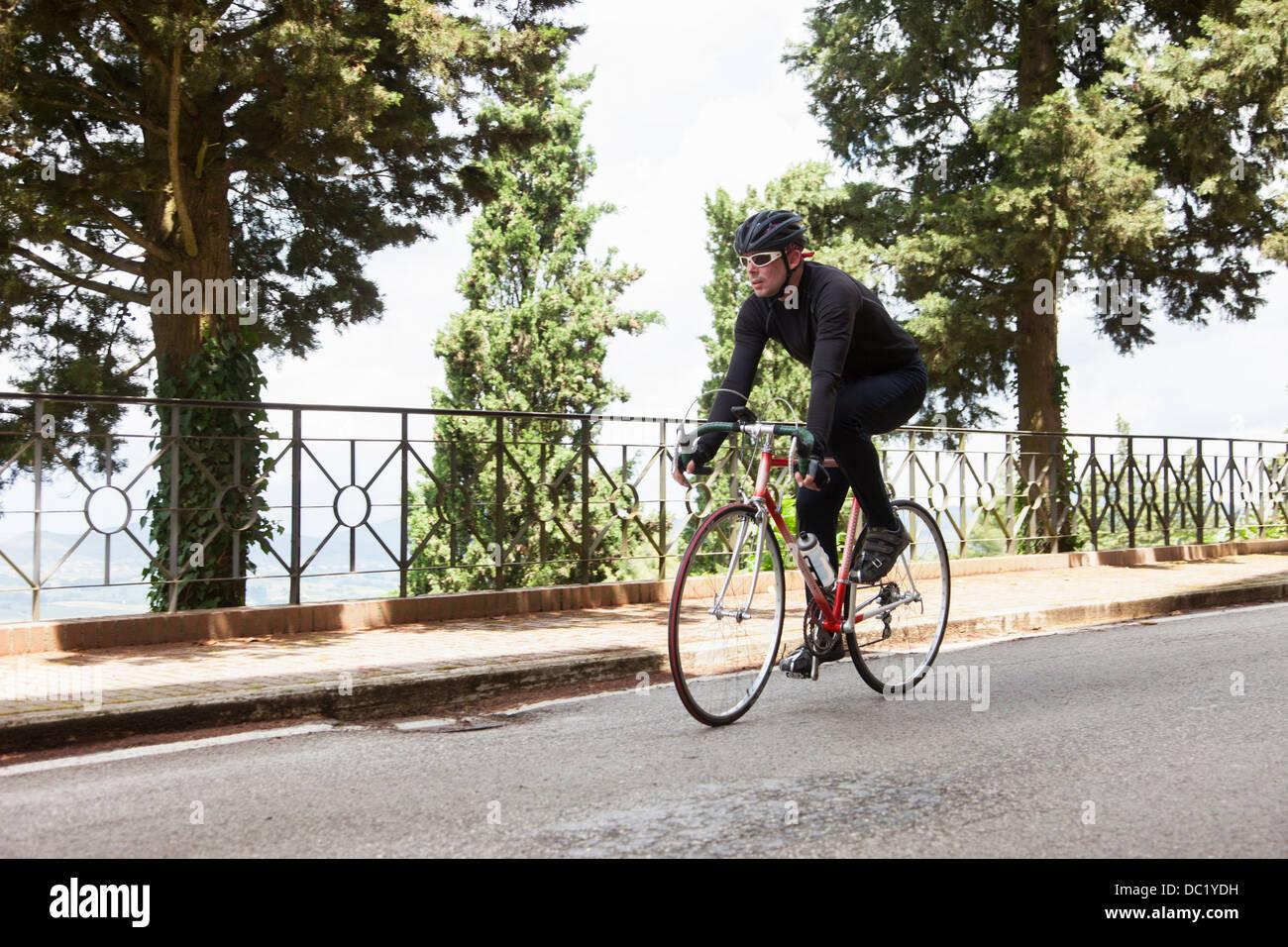 Ciclista riding down road in Umbria, Italia Immagini Stock