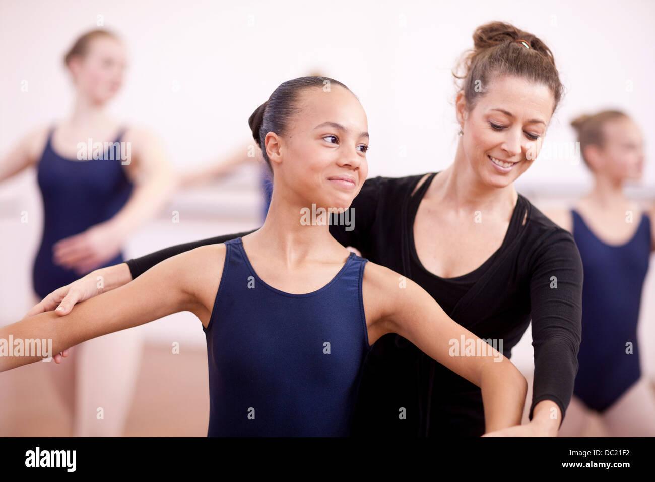 Insegnante di posa di regolazione del timido teenage ballerina Immagini Stock