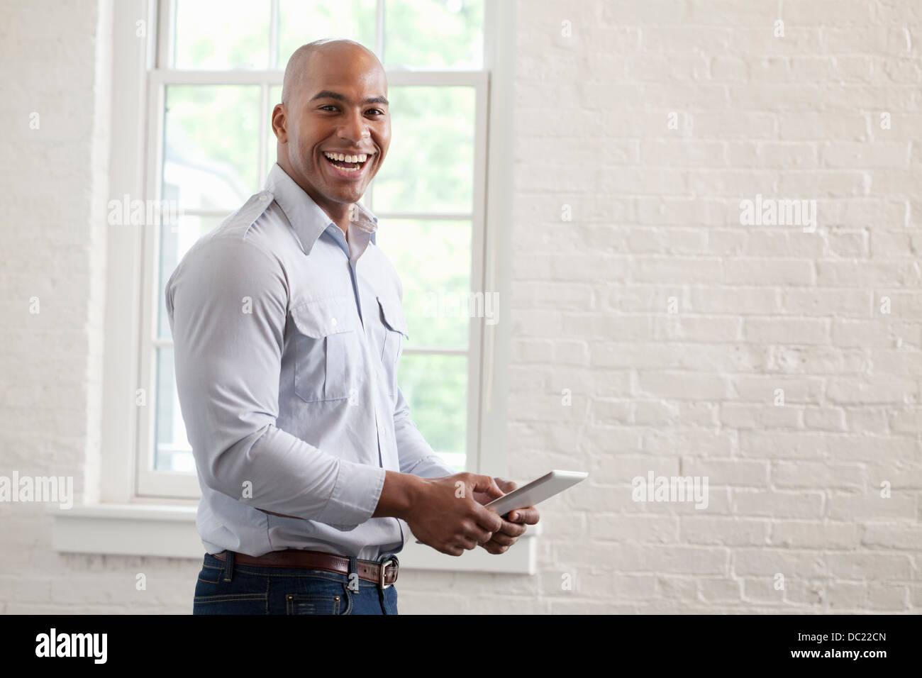 Metà adulto lavoratore di ufficio azienda digitale compressa e sorridente, ritratto Immagini Stock