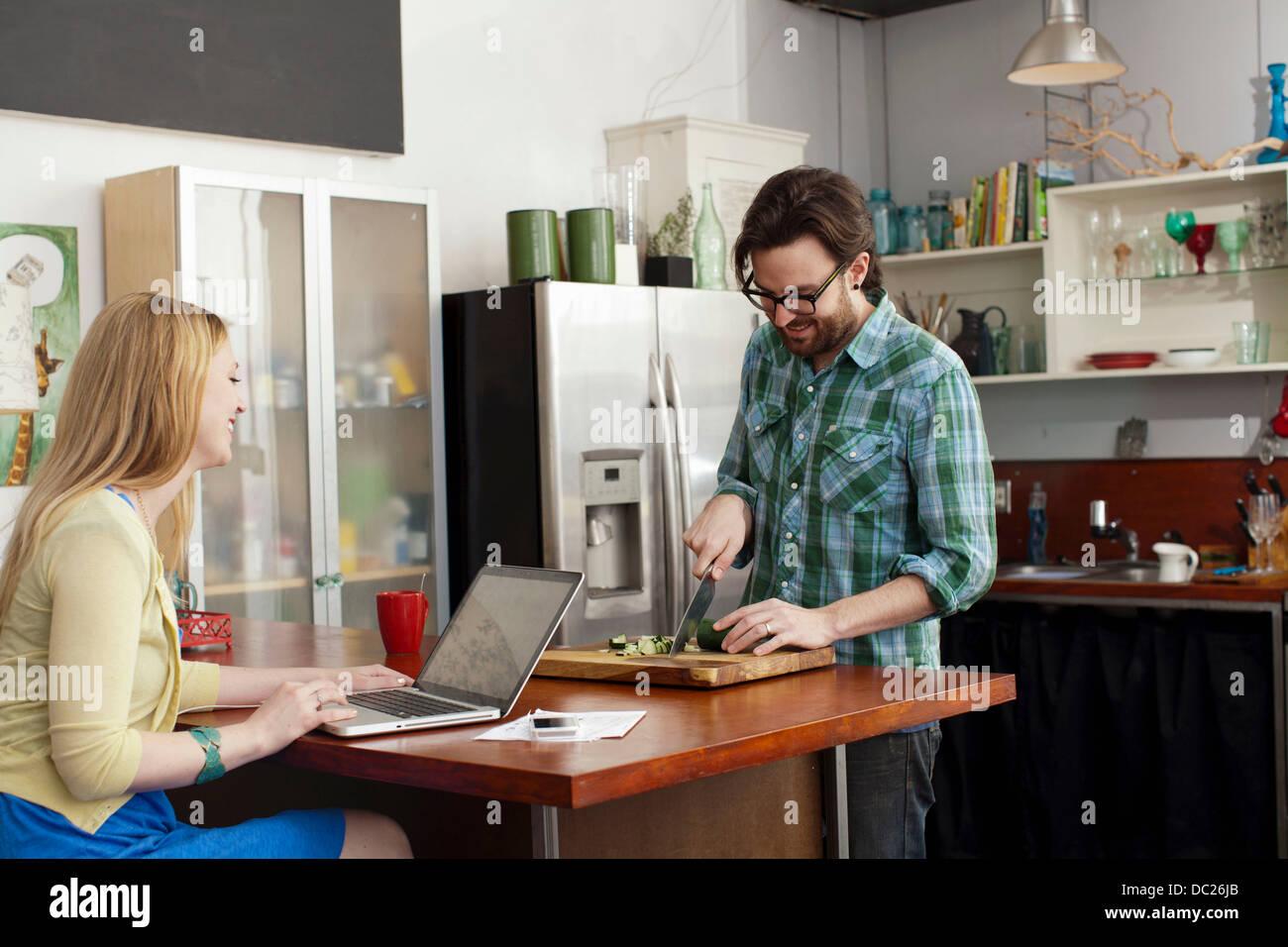 Donna al computer portatile, uomo tritare verdure Immagini Stock