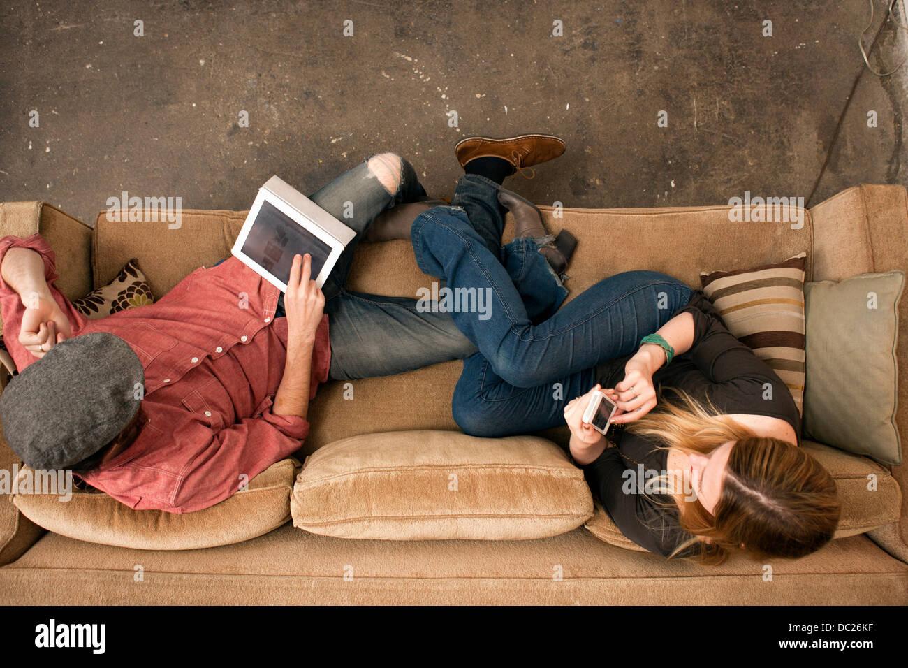 Giovane seduto sul divano con tavoletta digitale e lo smartphone Immagini Stock