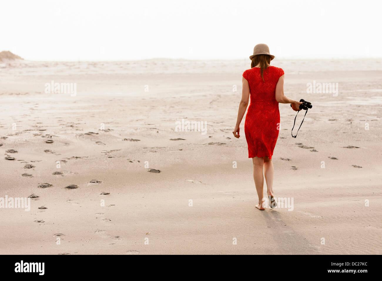 Donna matura indossando abito rosso camminando sulla spiaggia Immagini Stock