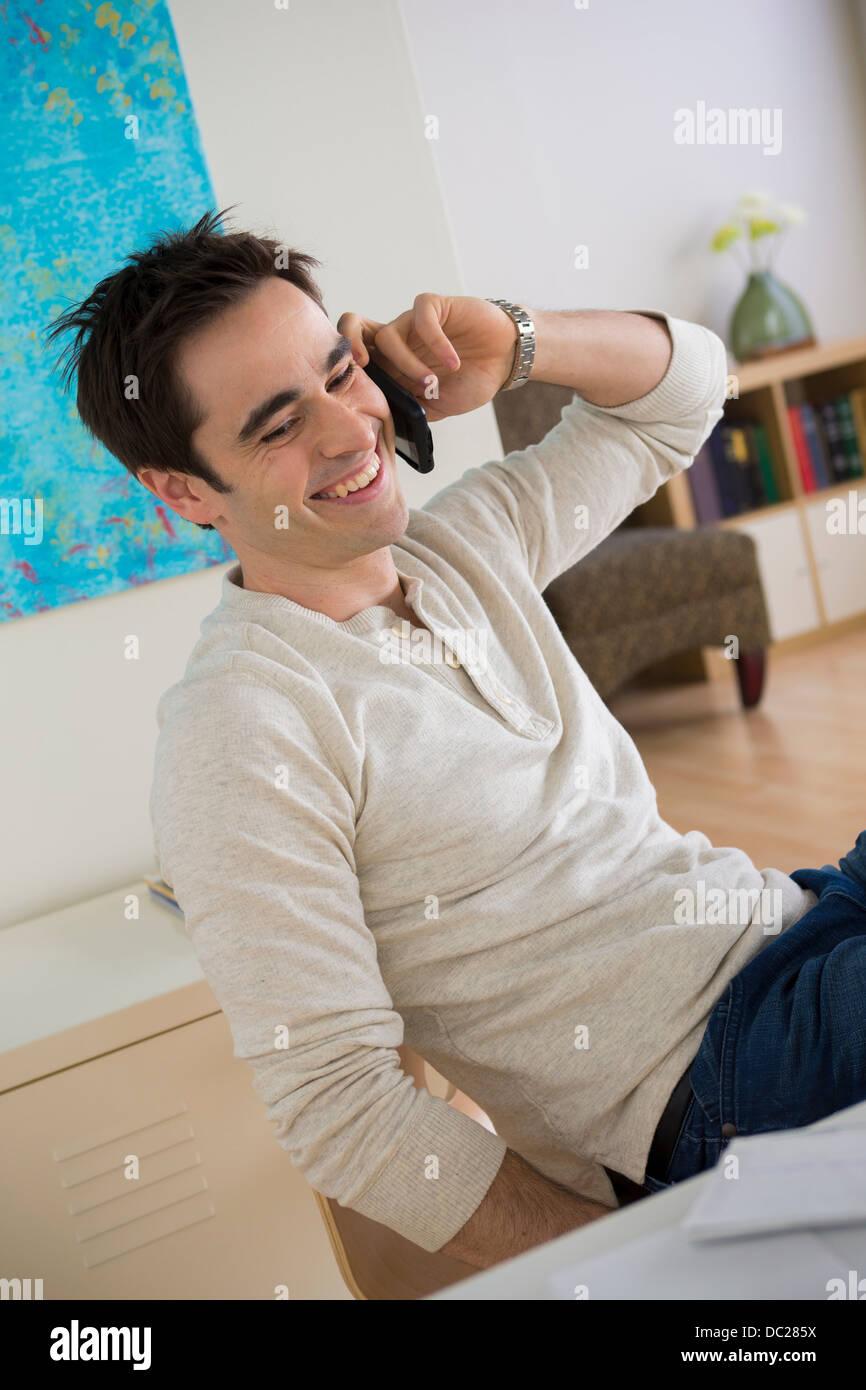 Metà uomo adulto su telefono cellulare in home office Immagini Stock