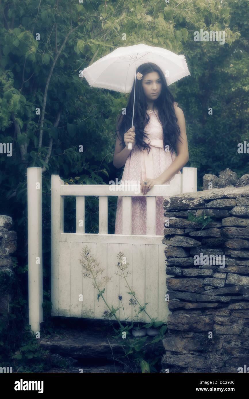 Una bella donna con lunghi capelli neri in piedi in un vintage abito rosa e un ombrellone dietro un cancello Immagini Stock