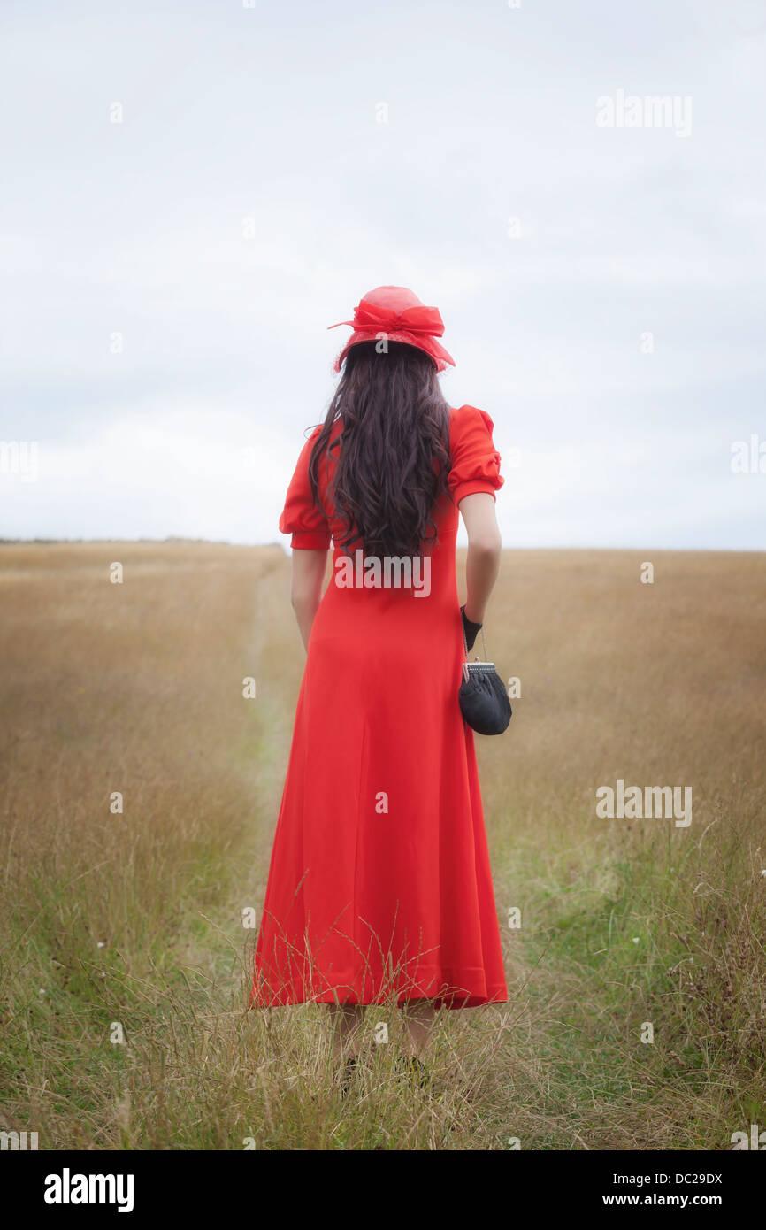 Una ragazza in un abito rosso è di camminare su un campo Immagini Stock