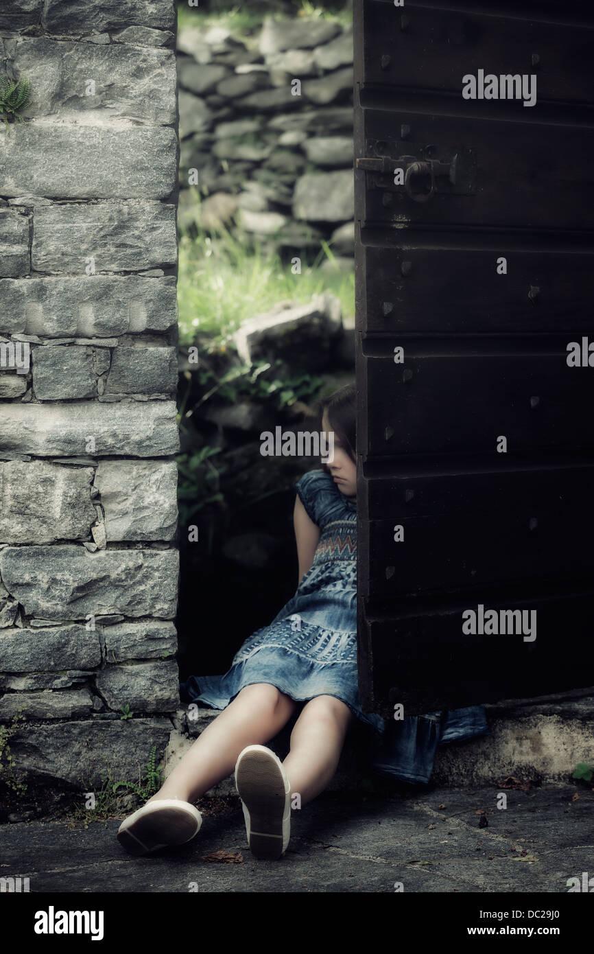 Un triste, giovane ragazza è seduta in una vecchia porta Immagini Stock