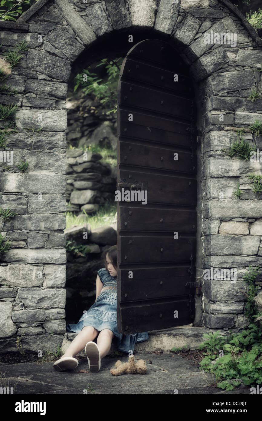 Un triste, giovane ragazza è seduta in una vecchia porta con un orsacchiotto di peluche Immagini Stock