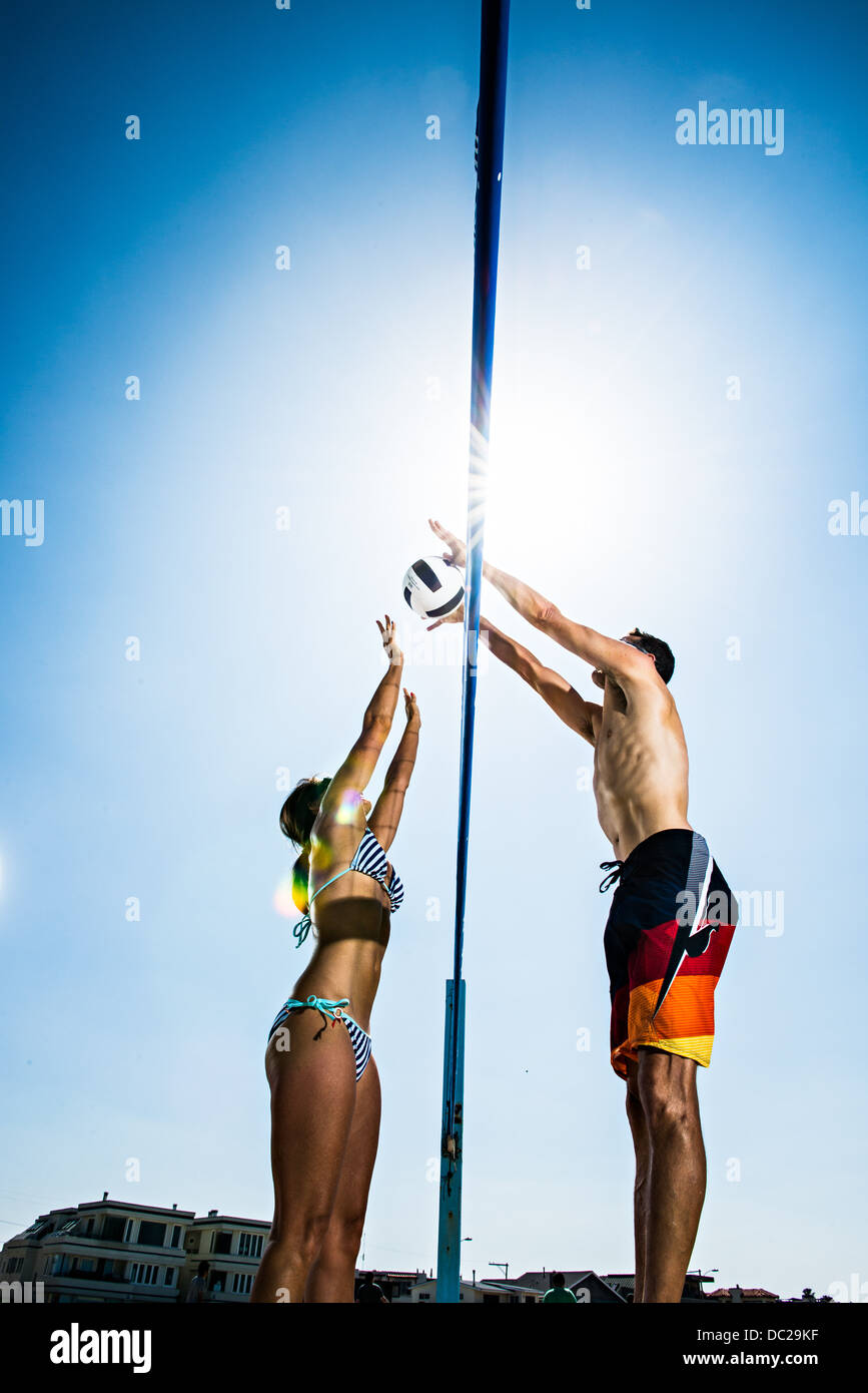 Due i giocatori di beach volley bloccando al netto Immagini Stock