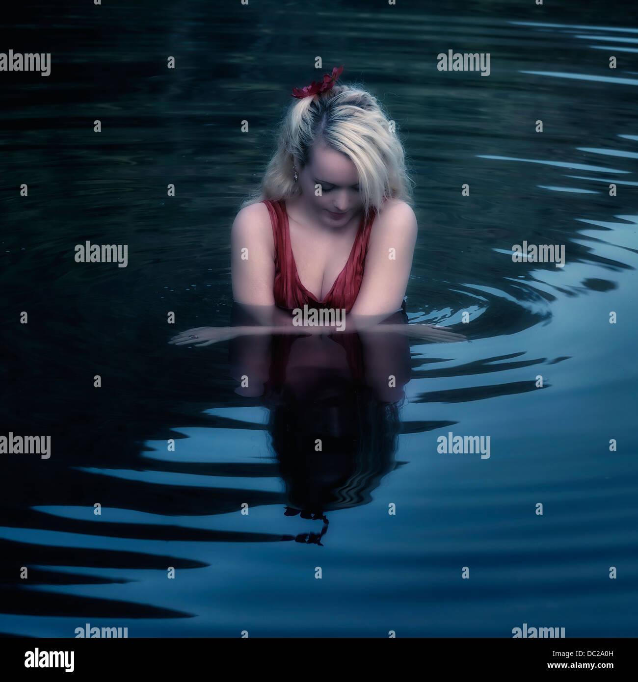 Una ragazza in un abito rosso è nuotare in un lago Immagini Stock