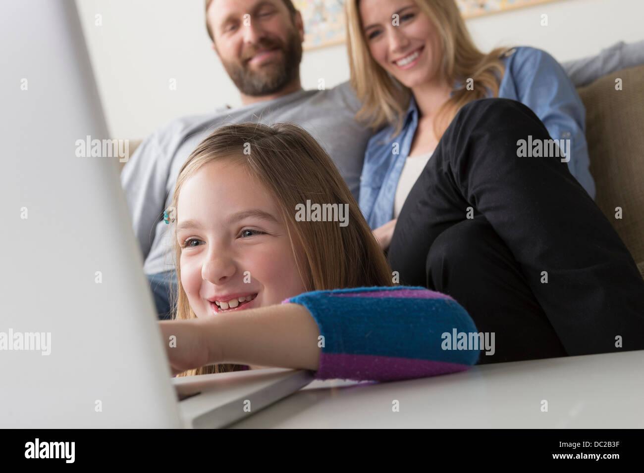 I genitori guardando il bambino utilizzando laptop Immagini Stock