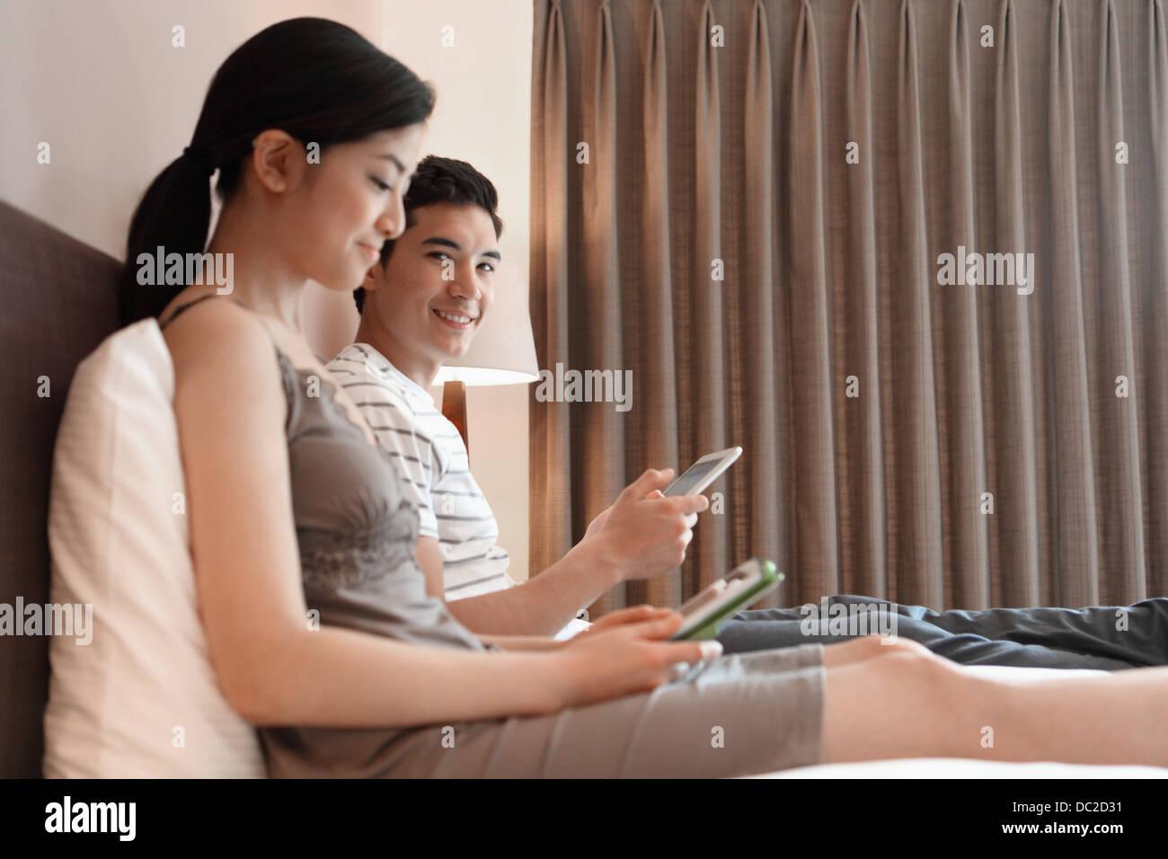 Accoppiare la navigazione in internet sul letto Immagini Stock
