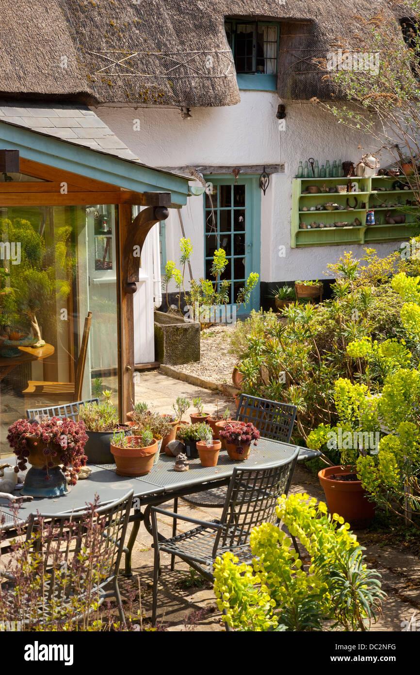 Garden Cottage patio con tavolo in metallo mobili e euphorbia piantagione e piante in vaso, Inghilterra Immagini Stock
