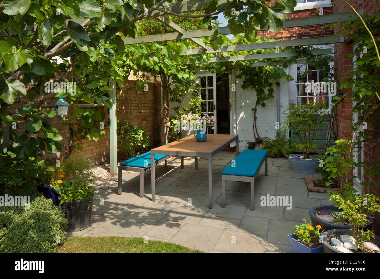 Contemporanea mobili da giardino sotto il pergolato di legno e ombreggiato patio nel giardino inglese, Inghilterra Immagini Stock