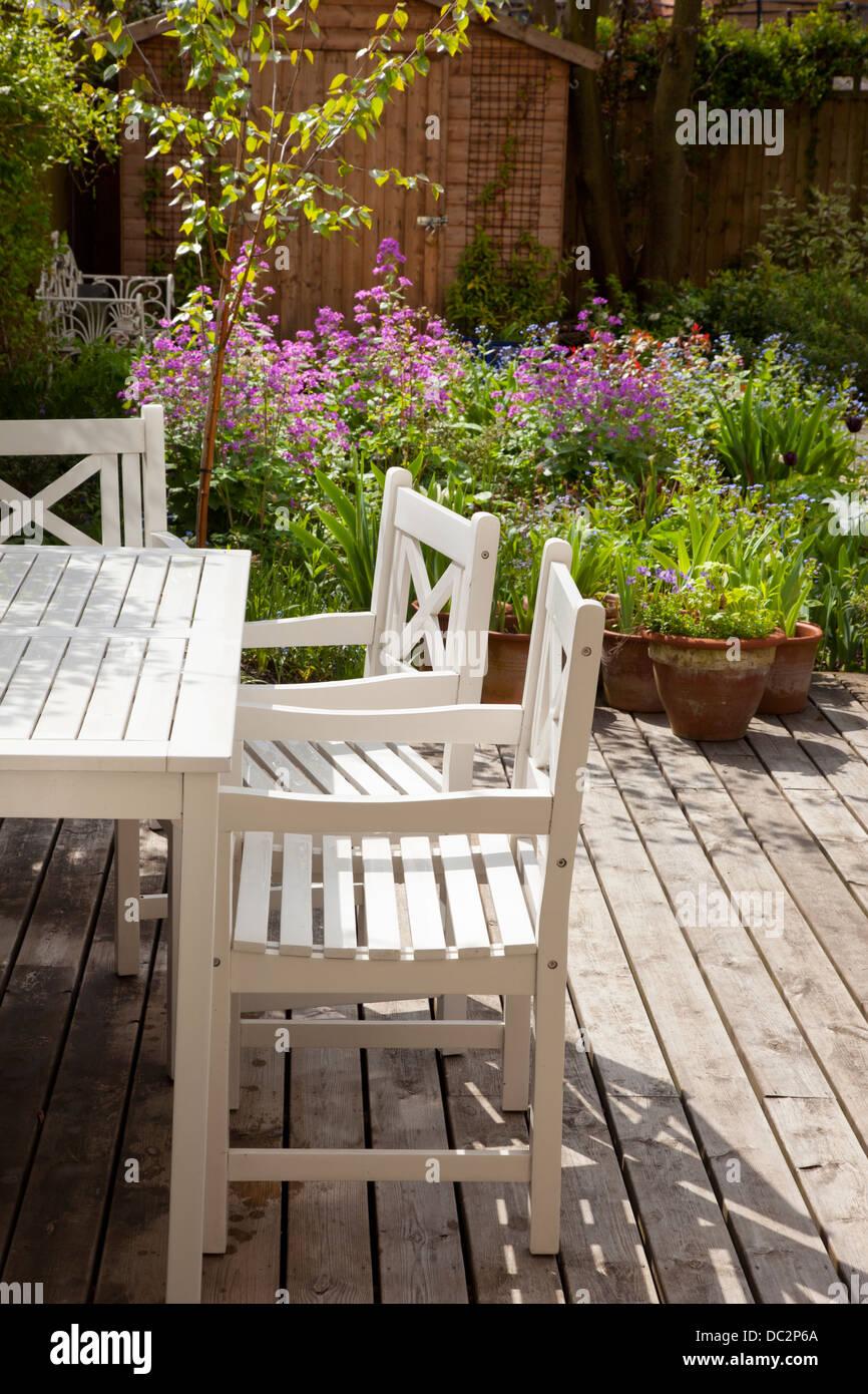 White mobili da giardino in legno e decking con estate boarder nel giardino inglese, Inghilterra Immagini Stock
