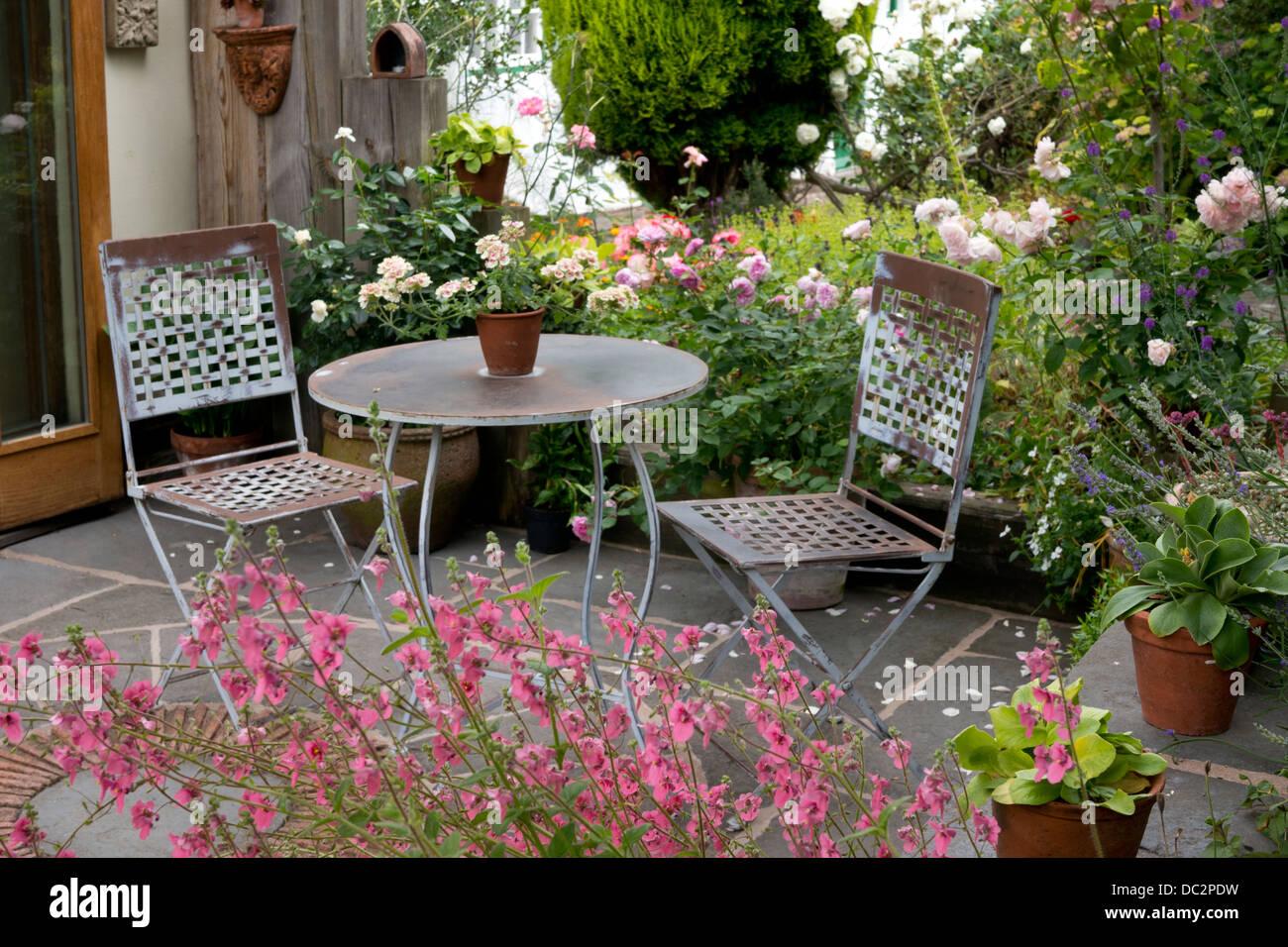 Inglese estate patio in pietra con metallo mobili da giardino orlato da rosa rose e fiori Diasica, Inghilterra Immagini Stock