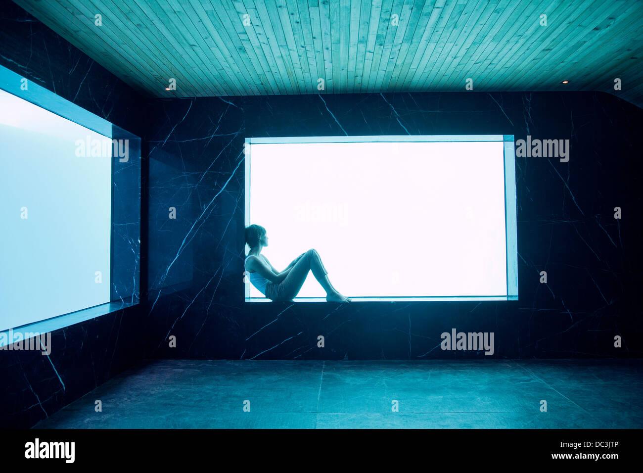 Donna seduta su mensola in corrispondenza della finestra in camera Piscina Immagini Stock