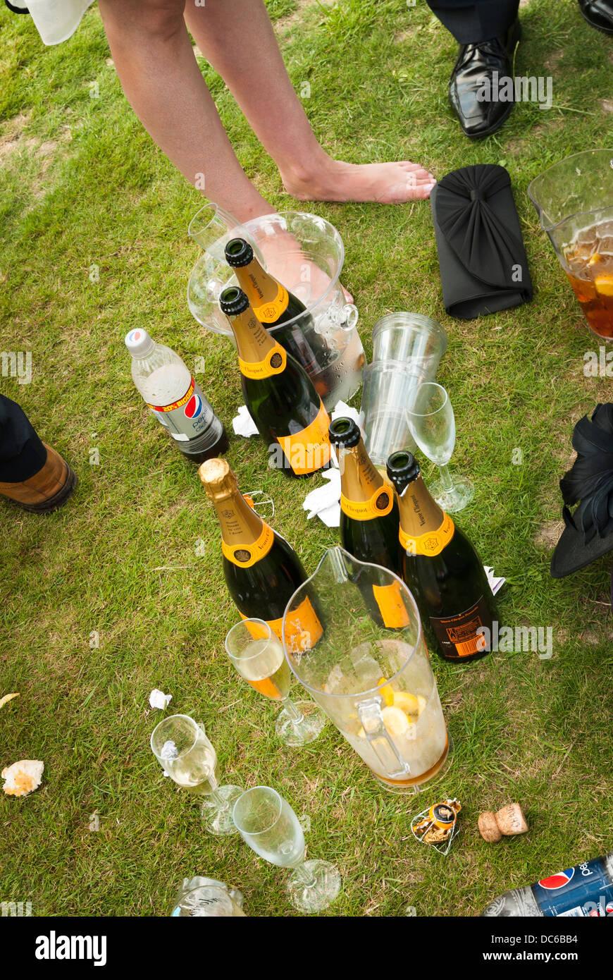 Aprire le bottiglie di champange sull'erba con signore a piedi nudi. Immagini Stock