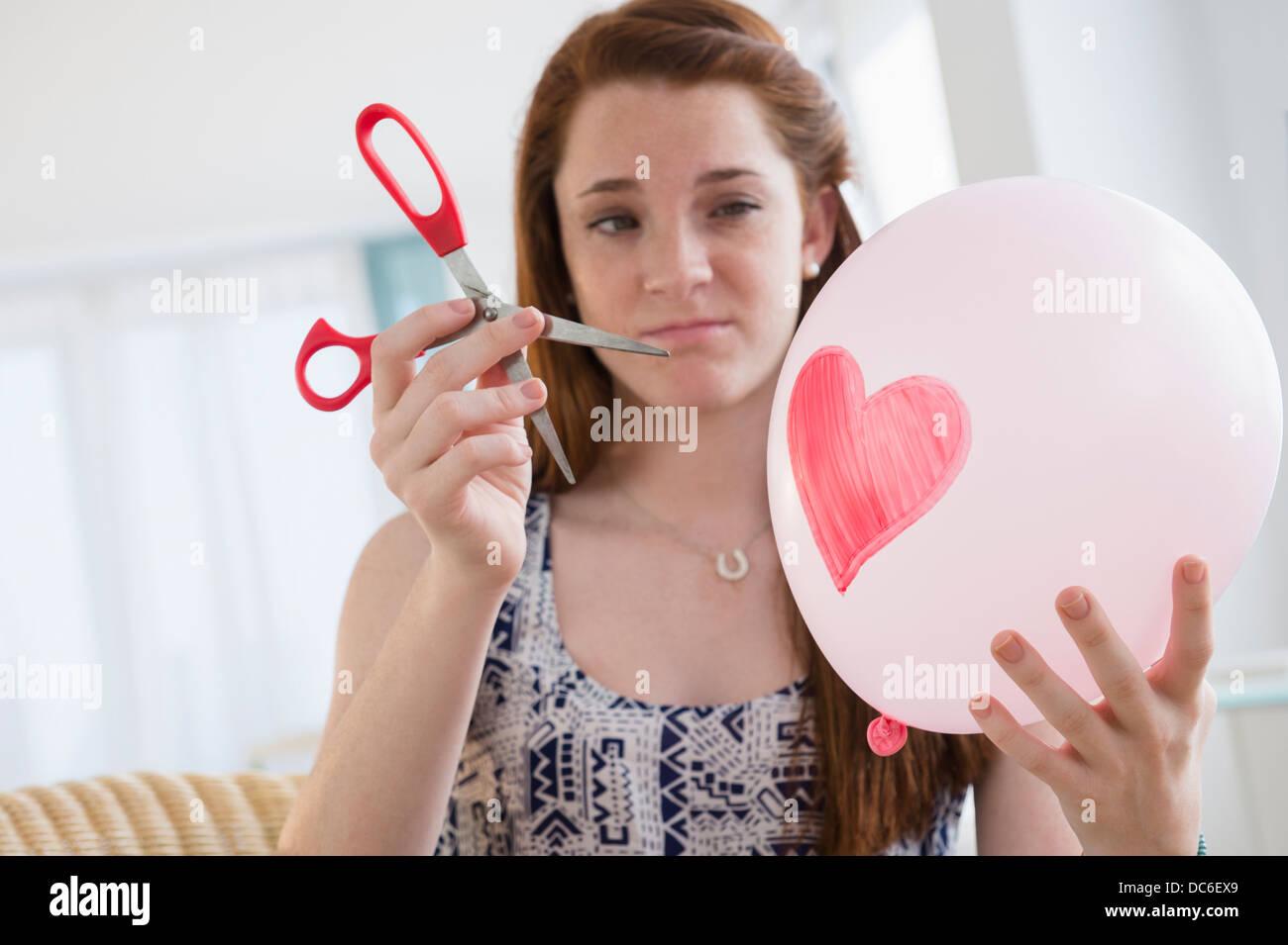 Ragazza adolescente (14-15) tenendo il palloncino e un paio di forbici Immagini Stock