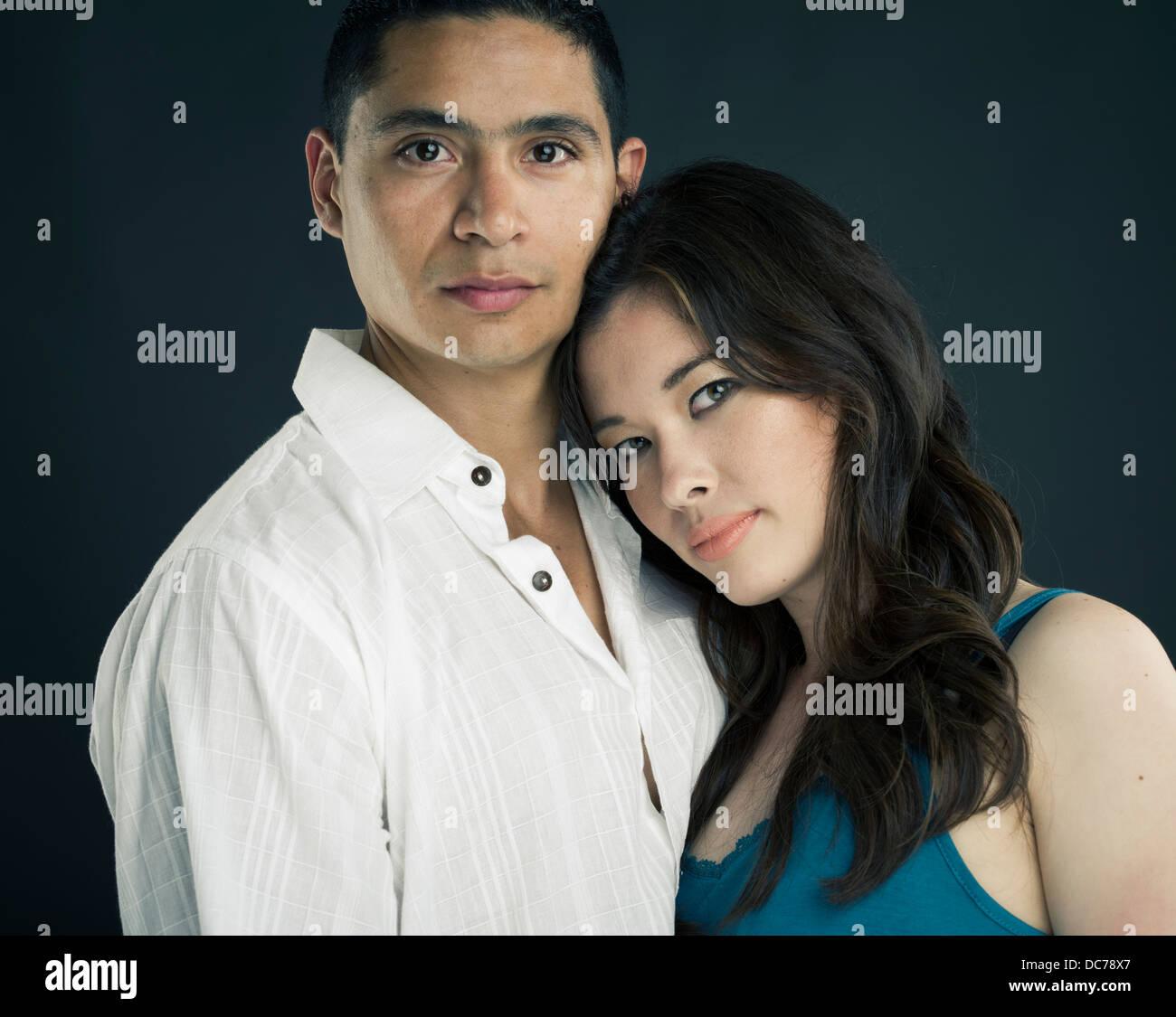 Razza mista bella giovane americano asiatico donna appoggiato la testa su latino uomo al torace / tracolla Immagini Stock