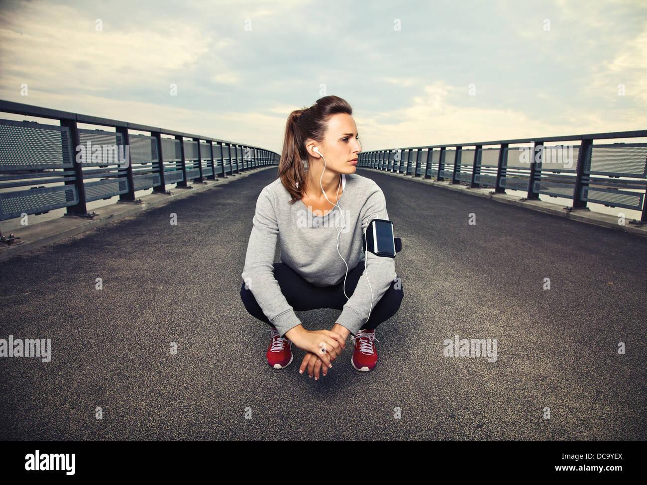 Runner donna seduta sul ponte dopo l'esecuzione Immagini Stock
