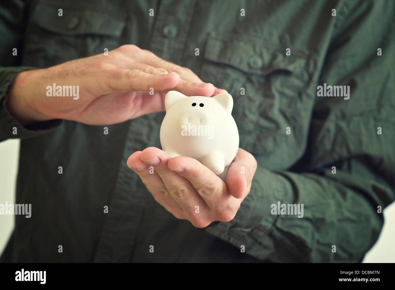 La mano di coccole white piggy coin banca con la paura di guardare nei suoi occhi. Immagini Stock